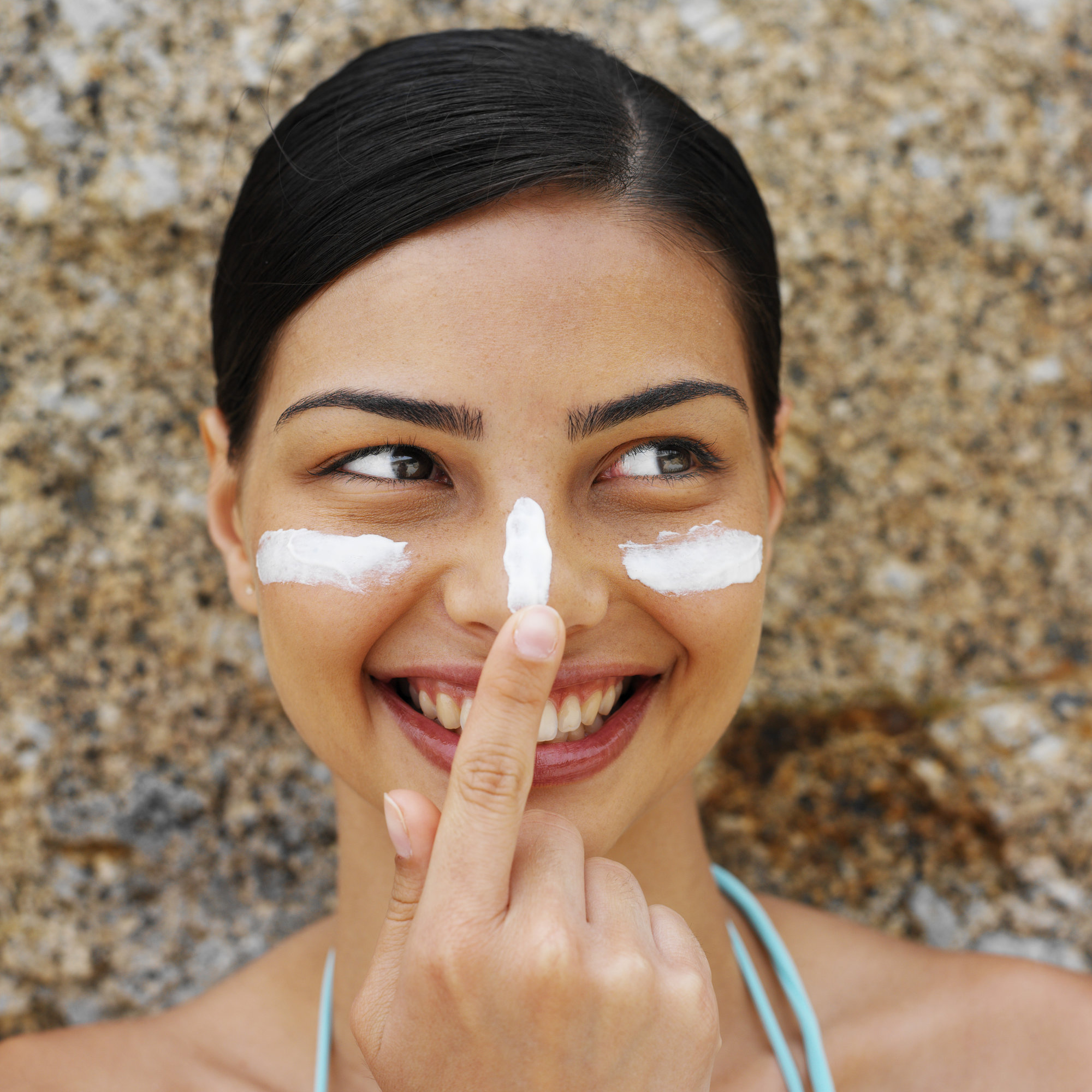 Front view portrait of a woman applying sun cream to her face